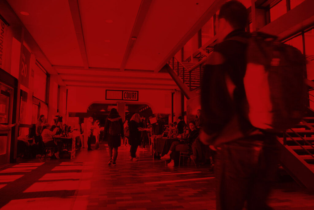 "Still from ""Students on the Issues That Matter Most to Them in the 2020 Presidential Election"" video; photo of students walking in the hallway leading to Union Court with red overlay."
