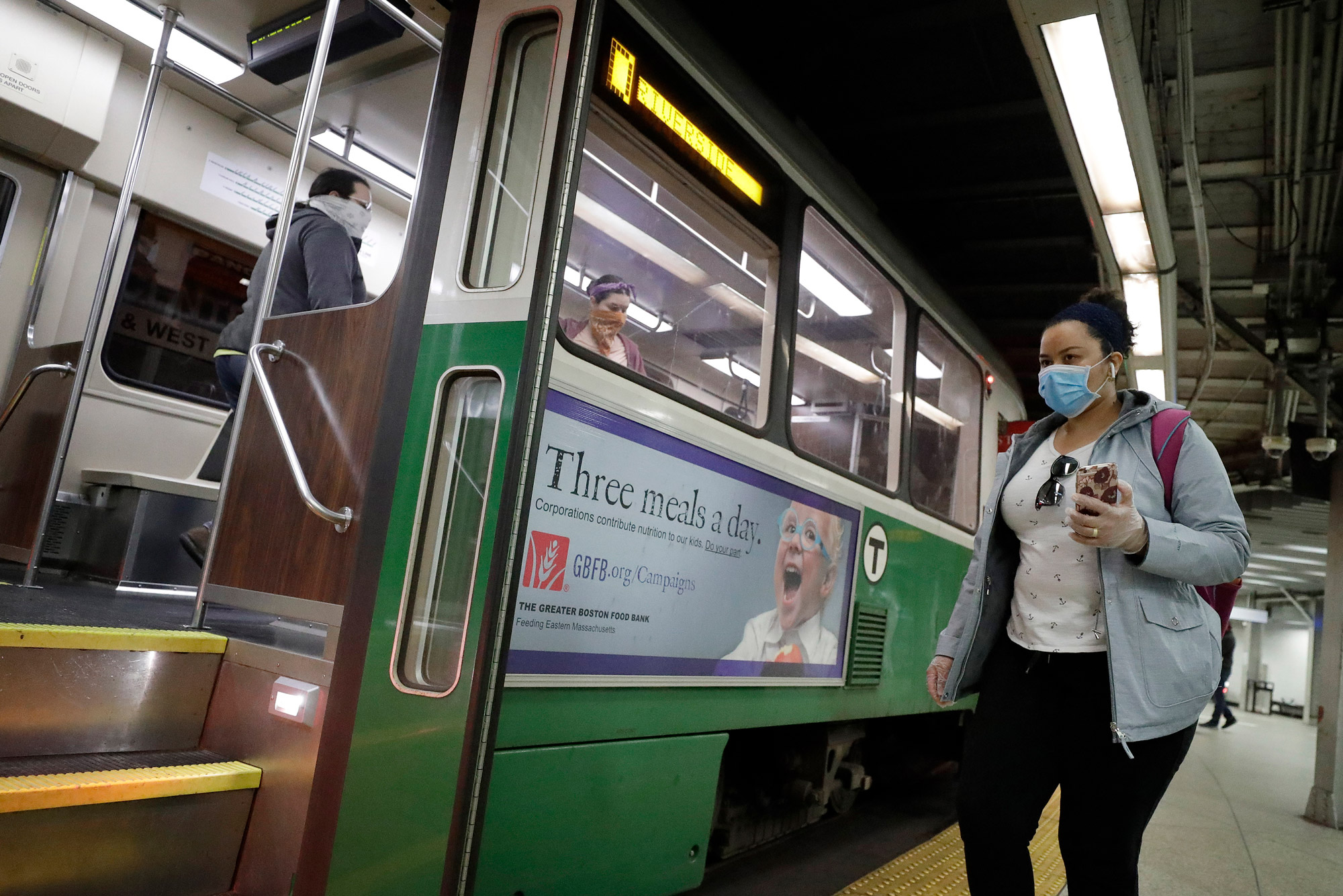 A photo of a woman in a mask holding her phone while she boards and MBTA green line train
