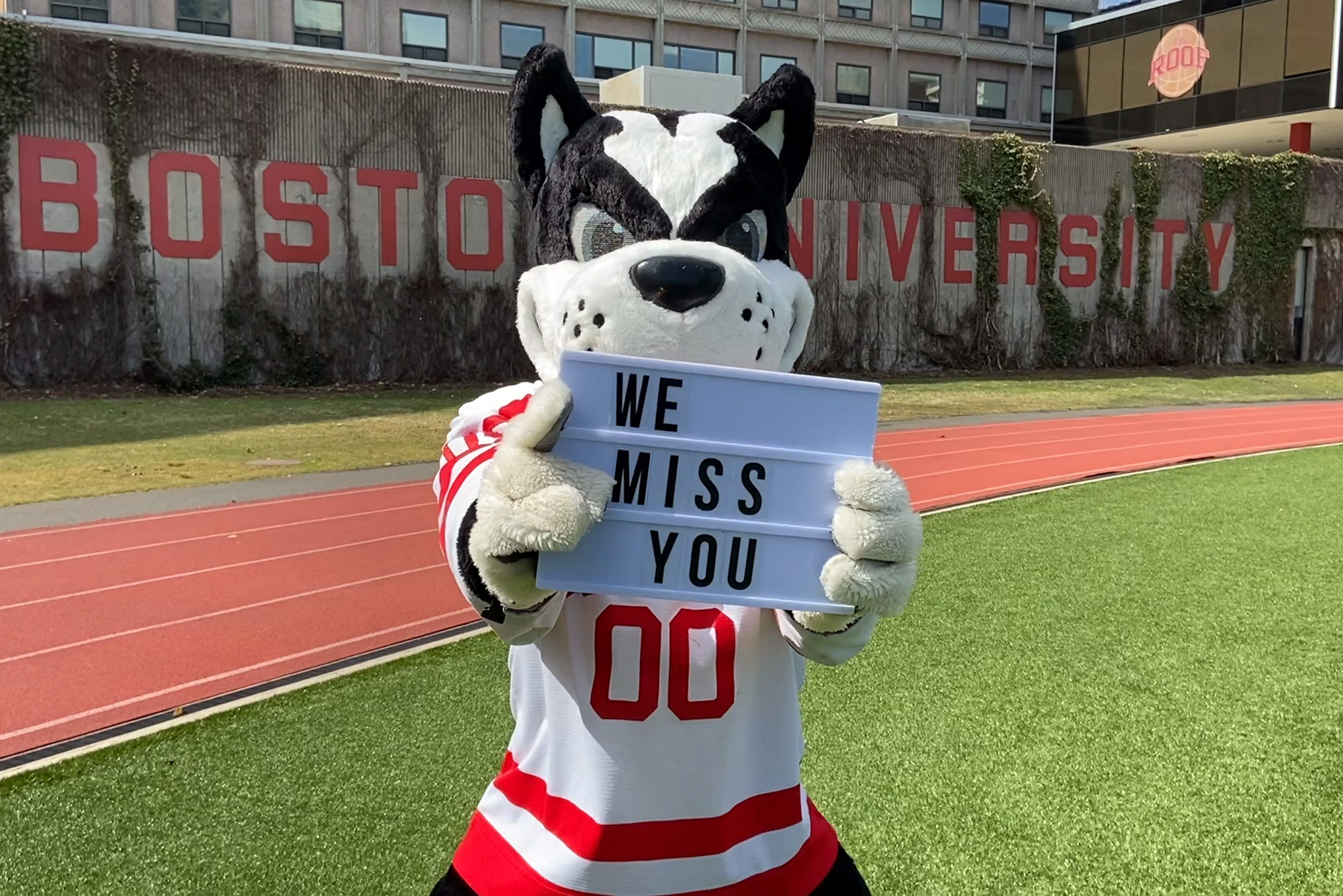 "A photo of Rhett holding a sign that reads ""We miss you."""