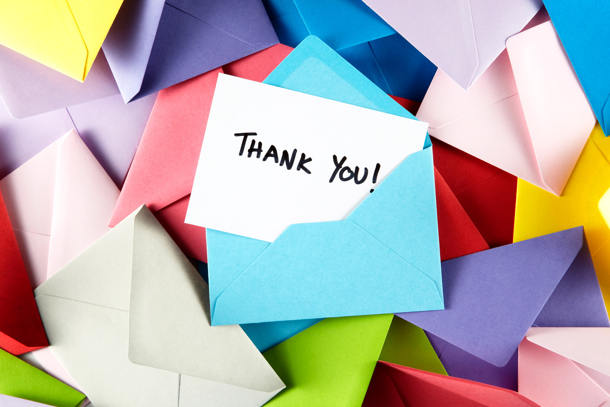 Image of a pile of colored envelopes with a note that says 'Thank You!' popping out of one.
