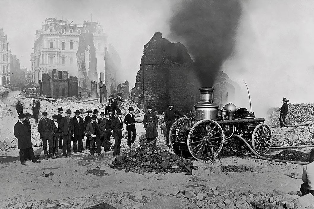 Black and white photograph of the Federal Street Post Office in the wake of the Great Boston Fire of 1872. A billow of smoke rises from the top of an old fire truck, a crowd of men stand close by.