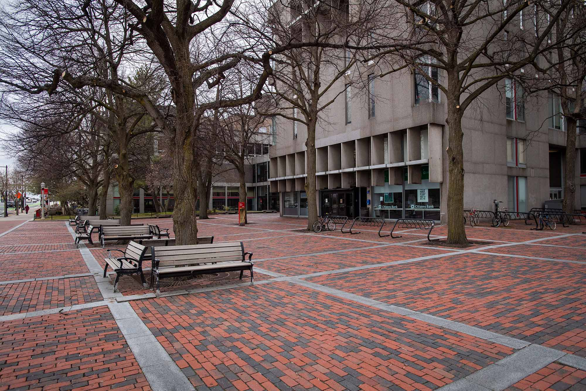 Shot of GSI Plaza in March 2020 on a rainy overcast day. Benches and bare trees are seen.