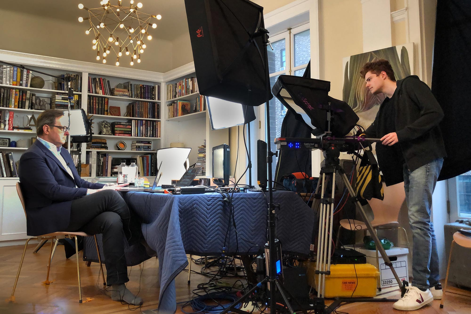 Photo of Nick Mason (COM'22) acting as a production assistant to his father, CBS This Morning co-host Anthony Mason, as they broadcast from their Manhattan apartment. Anthony is not wearing any shoes, and sits in front of a laptop with a suit jacket on.