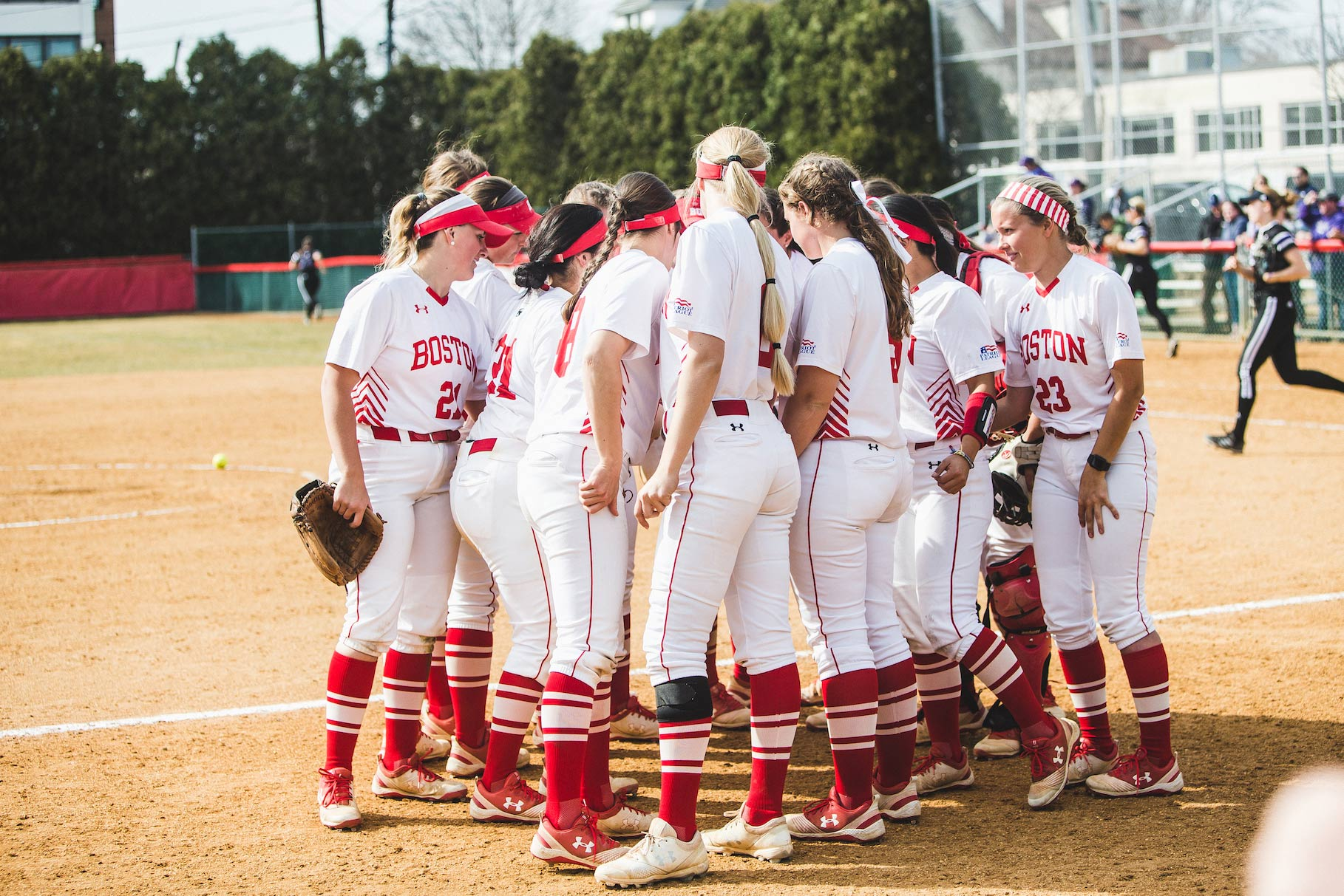 Photo of the BU softball team in a huddle. The team didn't get to play a single game at home, or even in New England, before the 2020 season was cut short by the coronavirus pandemic.