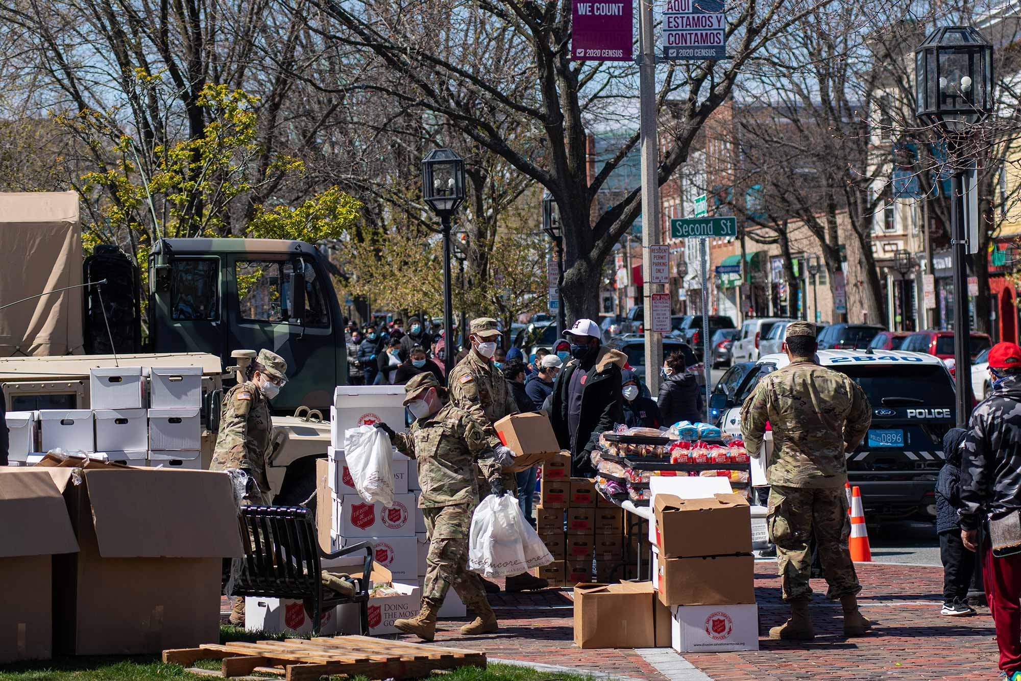 "Images of local volunteers along with the National Guard distributing food to locals at Winnisimmet Park in downtown Chelsea April 23, 2020. Many boxes say ""Salvation Army"" on the side, and a line of people with masks is seen in the background."