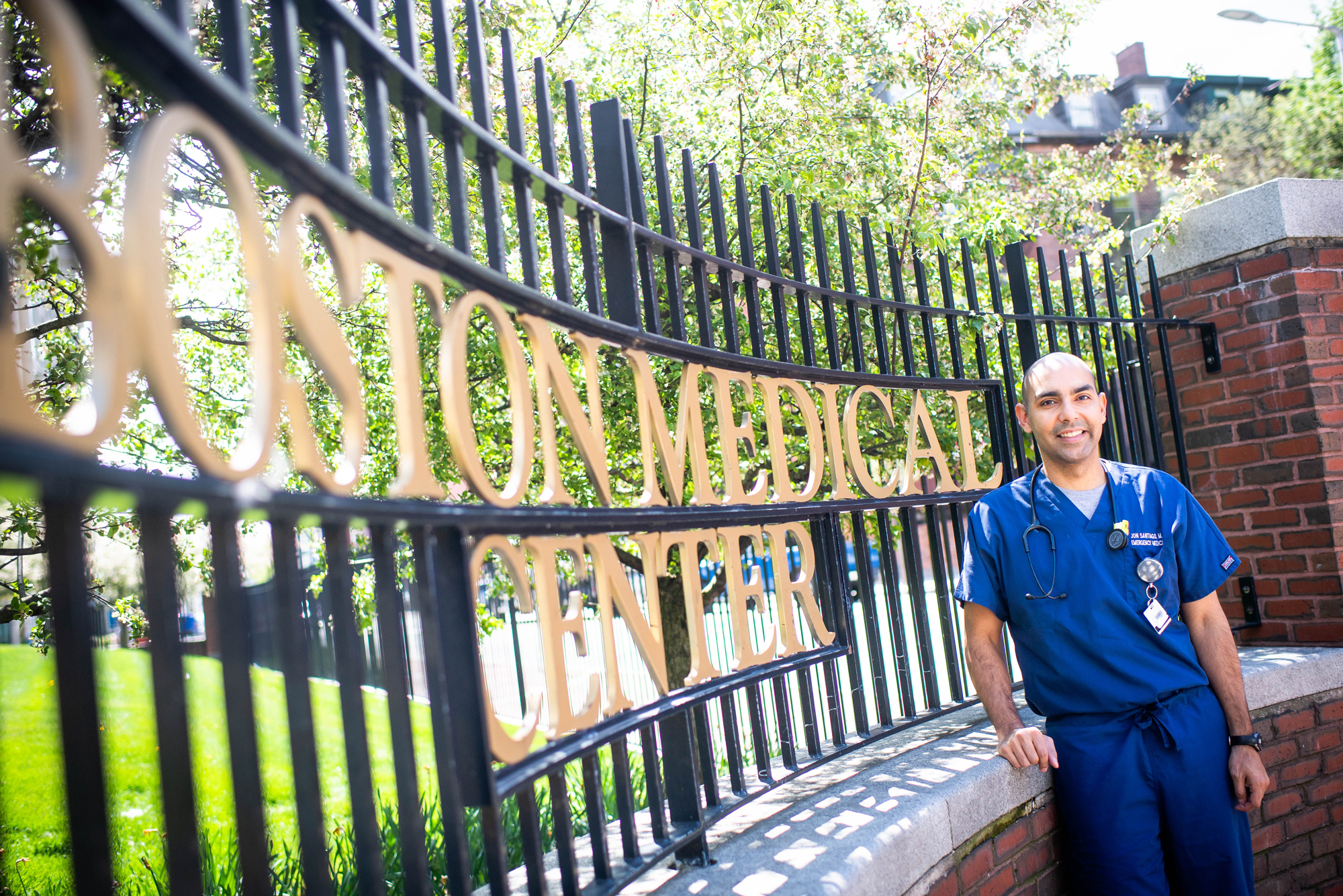 "A photo of Massachusetts State Representative Jon Santiago posing in front of a gate that reads ""Boston Medical Center"""