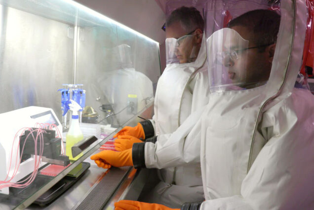 A photo of researchers working with COVID-19 in the NEIDL labs