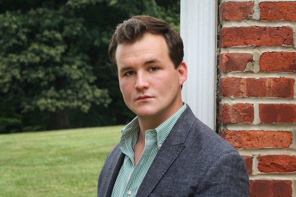 Portrait d'Eric Carey en blazer et chemise boutonnée. Derrière lui, un mur de briques et de l'herbe.