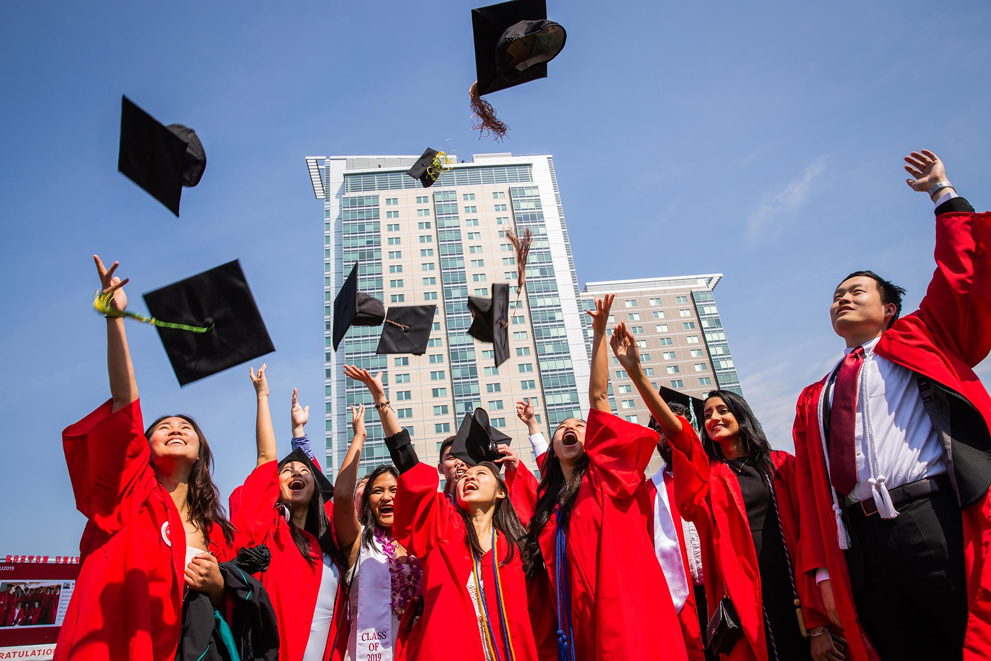 Photo of 2019 graduates at Boston University's Commencement on Nickerson Field on May 19, 2019 throwing their hats into the air. They are wearing red gowns. It's a sunny day and the sky is blue.