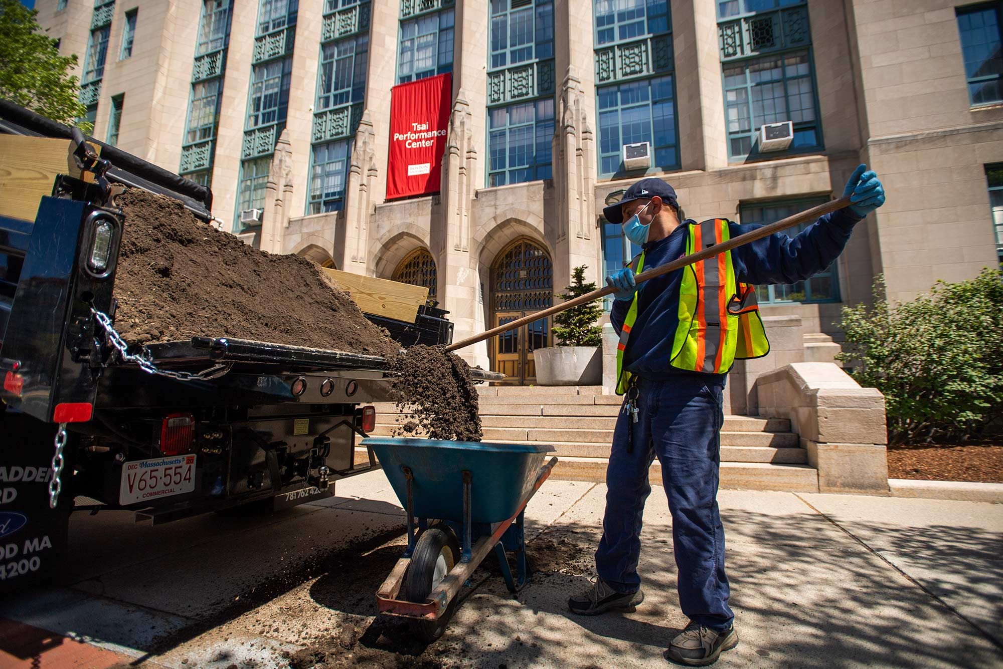 Image of Larry Herrera, of BU's Grounds crew, moving dirt into a wheelbarrow to lay grass seed along CAS on May 13, 2020. He wears a mask, baseball cap, and reflector vest.