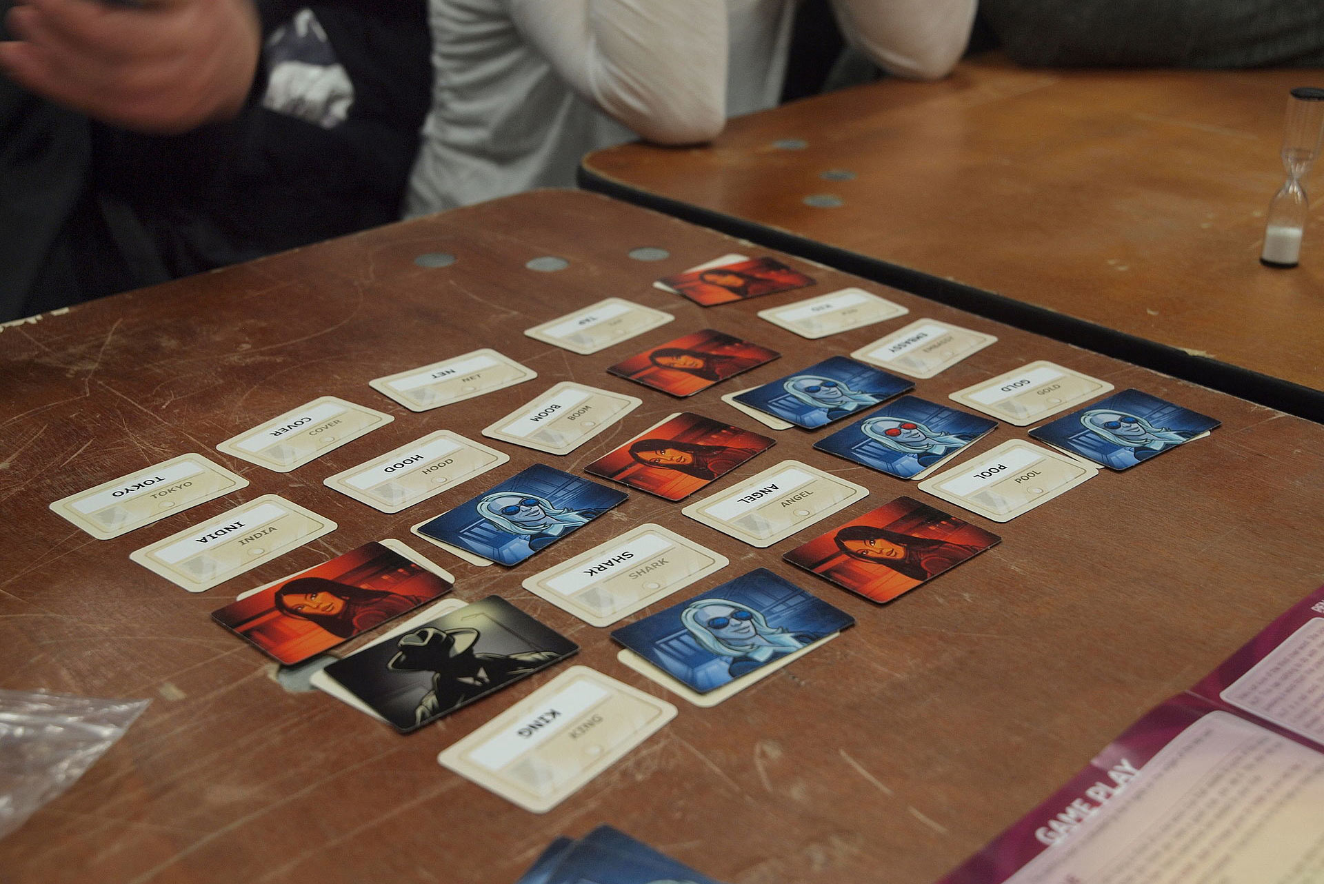 Photo of a game of Codenames being played at the annual board game festival of Finland in Helsinki, Finland. Some cards in the five by five grid show words, while others have blue, red and black illustrations of people.