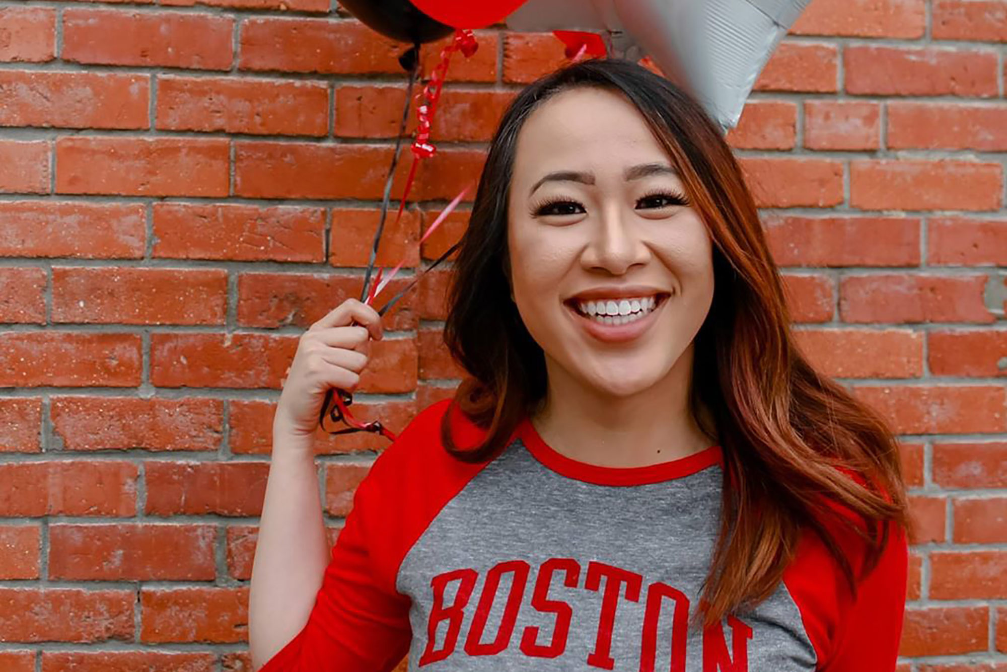 A photo of Geneve Lau holding scarlet and white balloons and wearing a Boston University shirt
