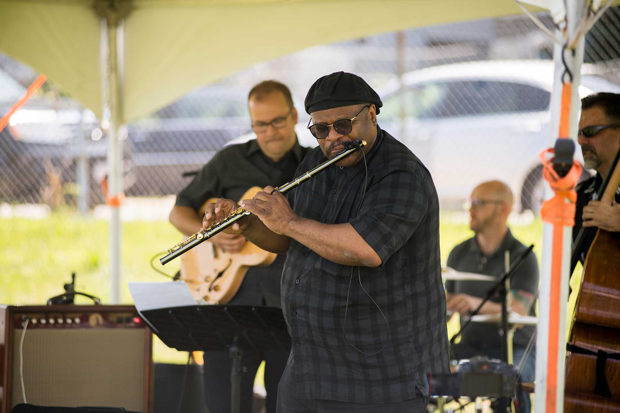 Photo of Lance Martin and The Lance Martin Trio perform during JazzFest in West Roxbury last year. Martin plays a flute, a bassist and drummer are seen in the background at an outdoor venue.