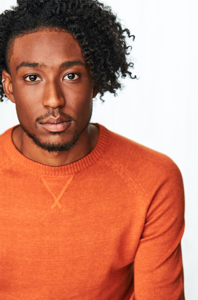 Portrait de Nicholas Walker dans une chemise orange vif.