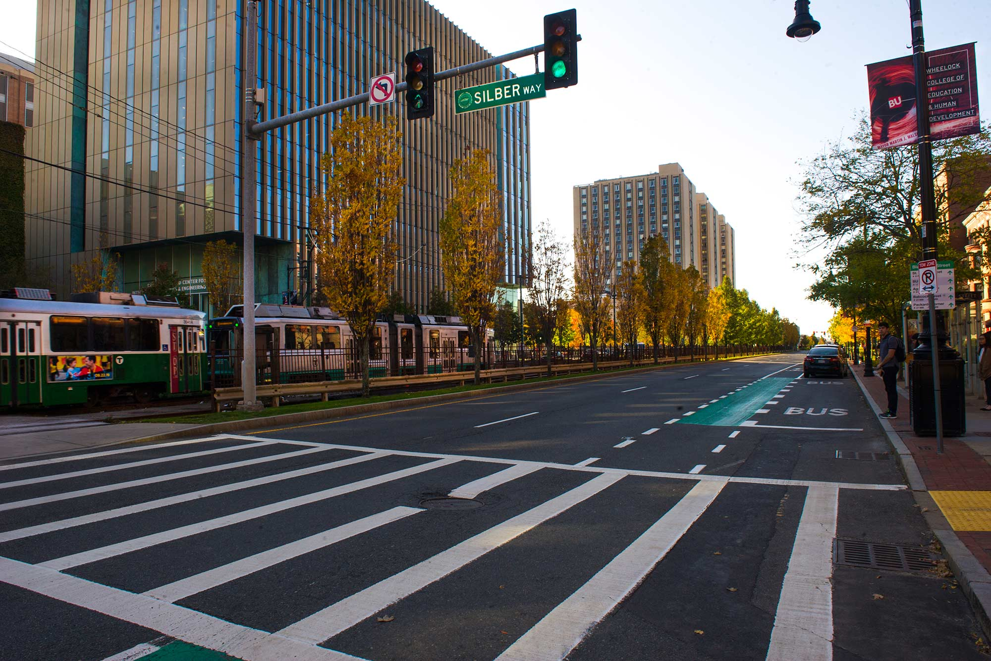 Photo of Commonwealth Avenue in East Campus by Silber Way. The T passes by and the trees look golden. Students wait at the BU BUS stop. Warren towers and Wheelock College banners are seen in the background.