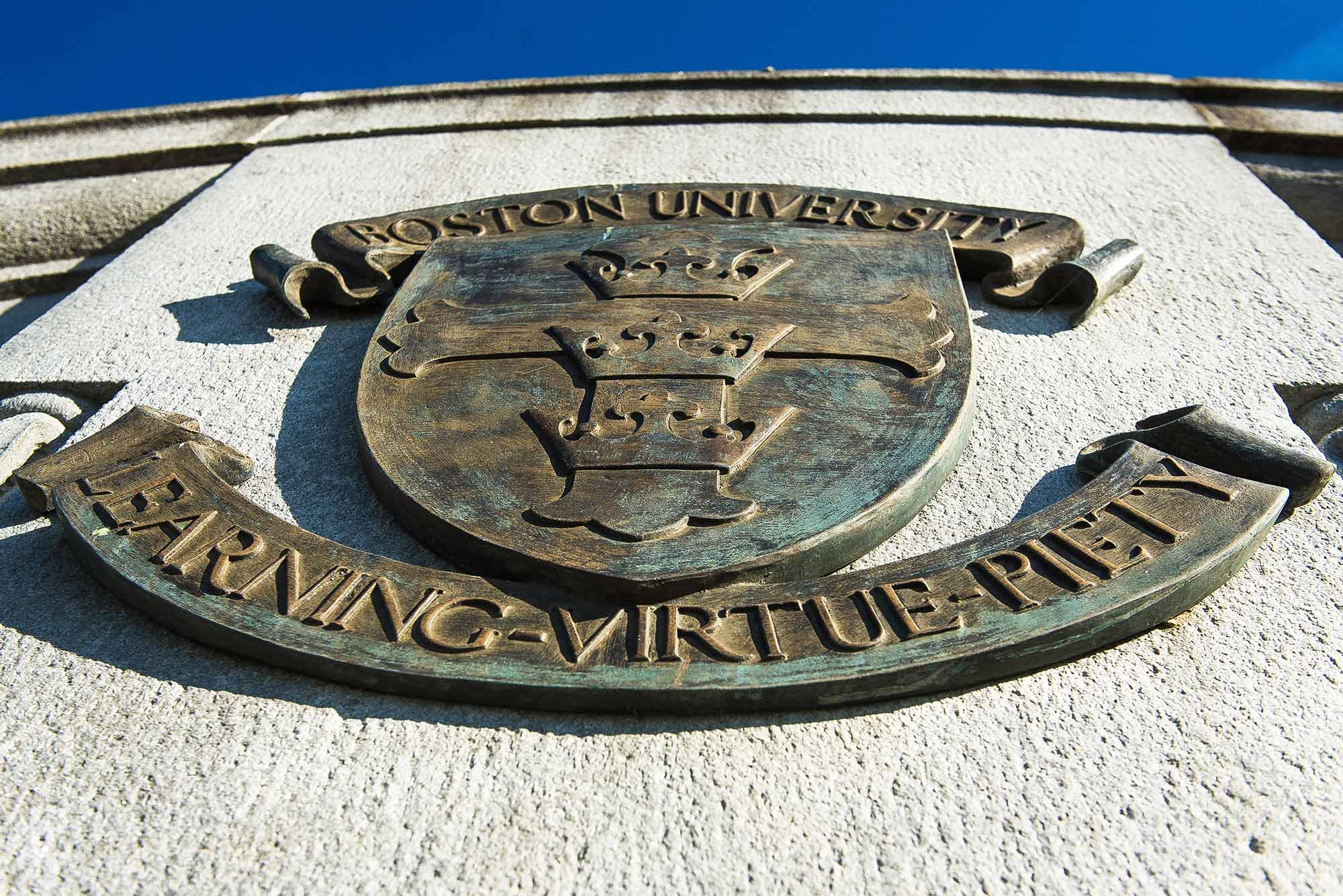 "Photo of rusting, greenish gold BU seal on a stucco wall from underneath. Seal reads ""Boston University, Learning, Virtue, Piety"""