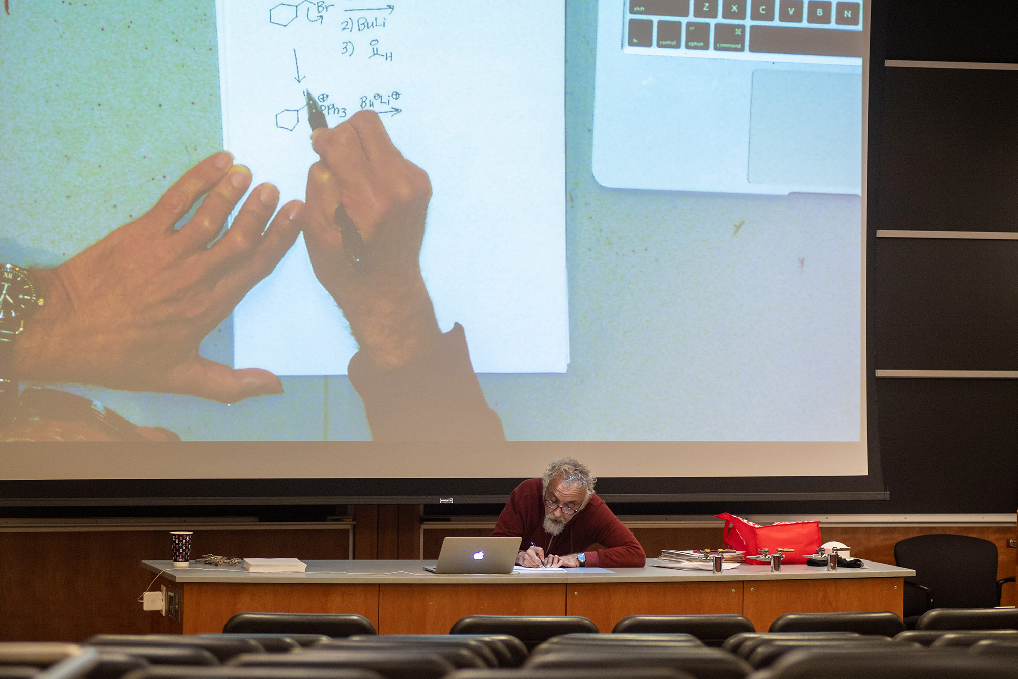 Photo of Bruno Rubio (GRS'96), a CAS master lecturer in chemistry, holding remote office hours for students in March. Rubio sits at a desk at the front of a lecture room and his hands working on a chemistry problem are seen on a projector screen behind him.