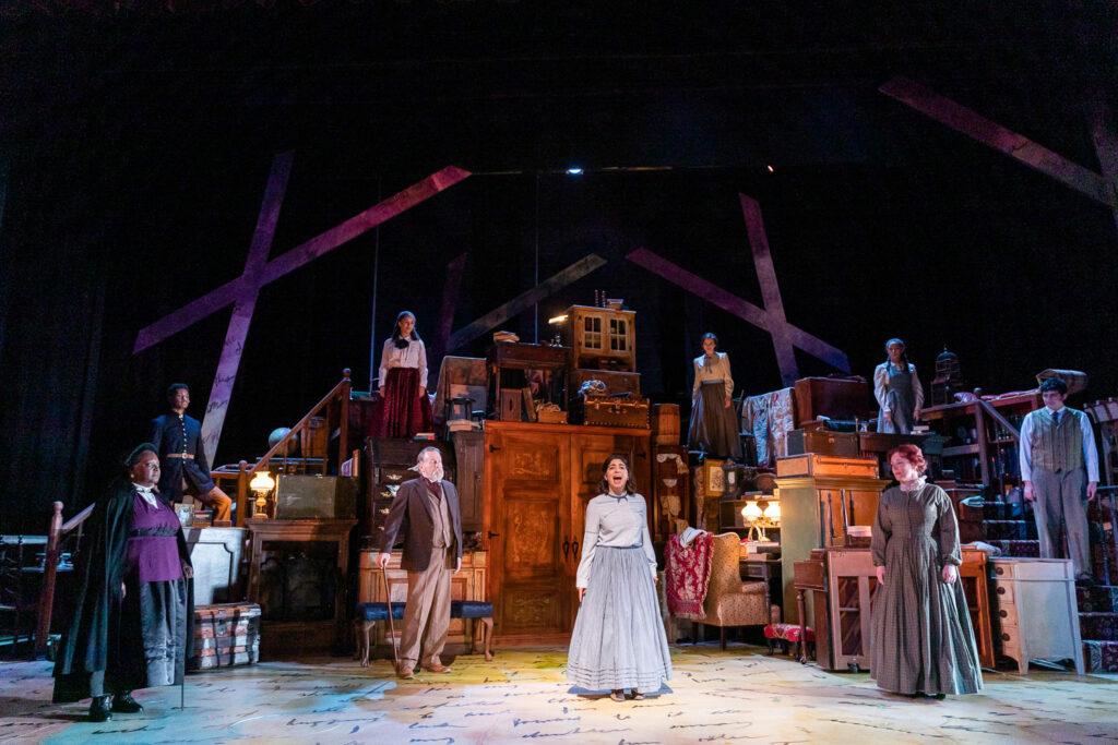 Scénographie de Martinez pour la production 2020 de Wheelock Family Theatre de Little Women: The Broadway Musical. Un groupe de personnes vêtues du 20e siècle est dispersé sur une scène à plusieurs niveaux.