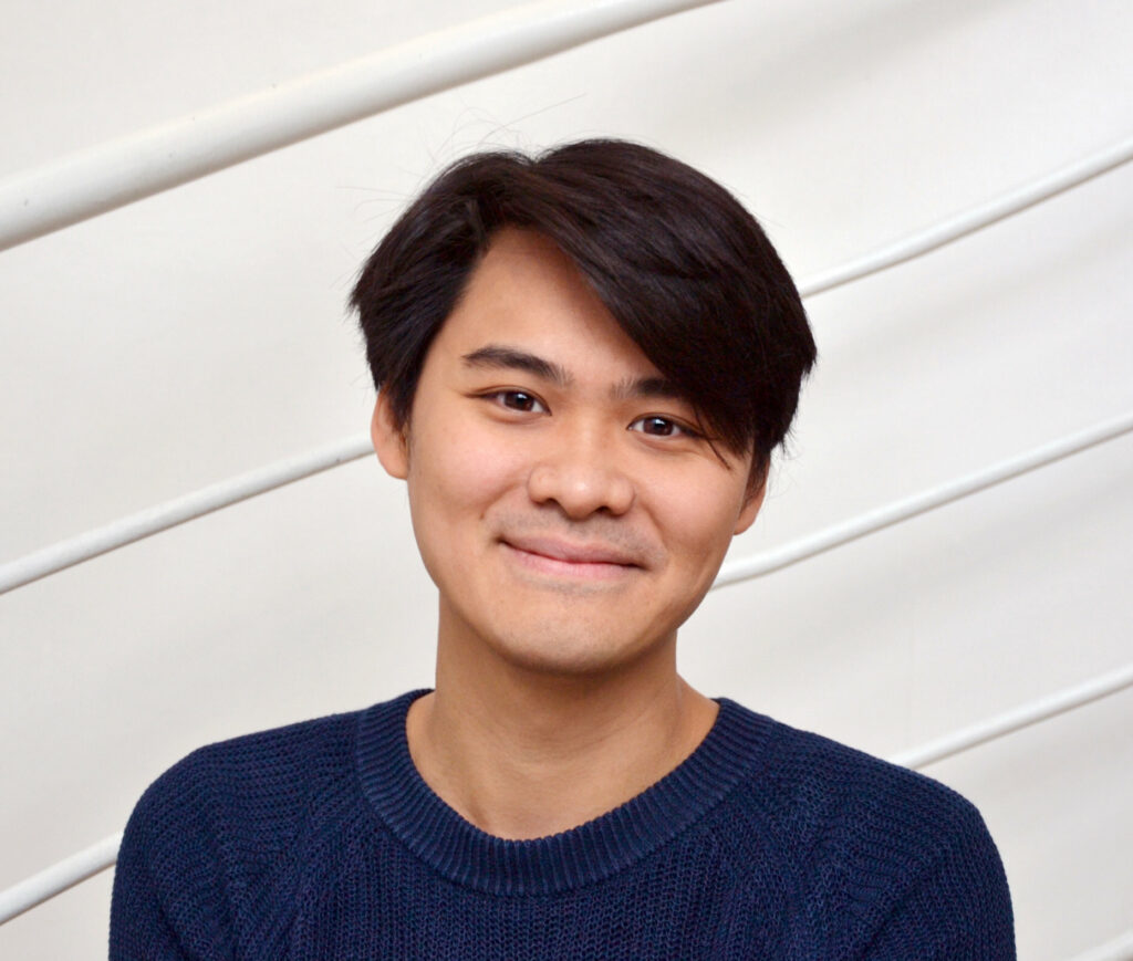 Portrait de Tak-Cheung Hui dans une chemise bleue sur fond gris dépouillé.