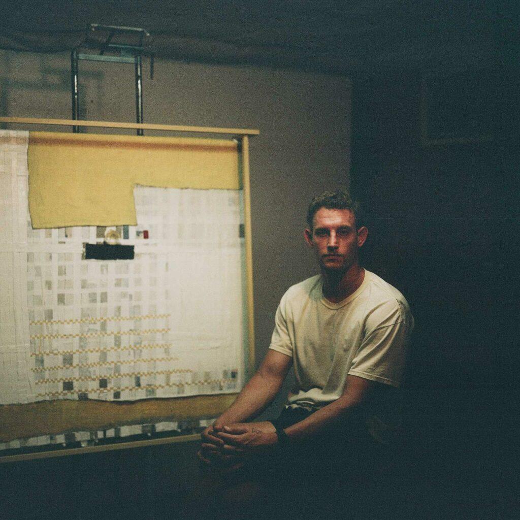 Photo d'Alex Stern dans son atelier à côté d'un chevalet. Il est assis avec ses mains croisées sur son genou.