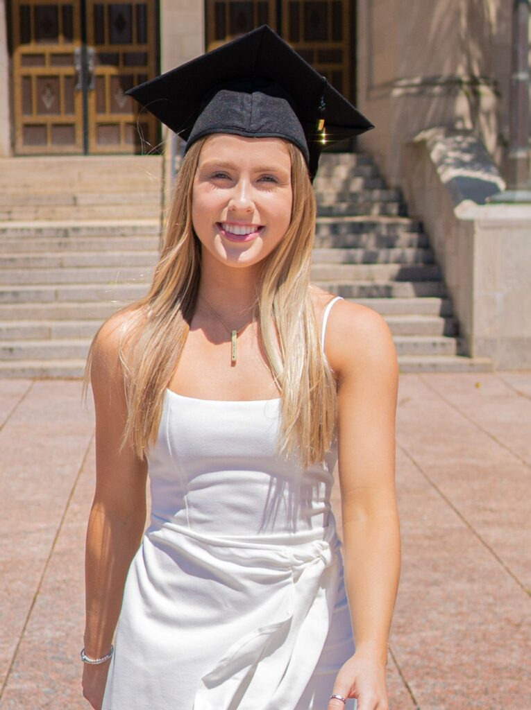 Photo of McKenzie Beaton (SAR'20) in a white dress and black graduation cap in front of Marsh Chapel.