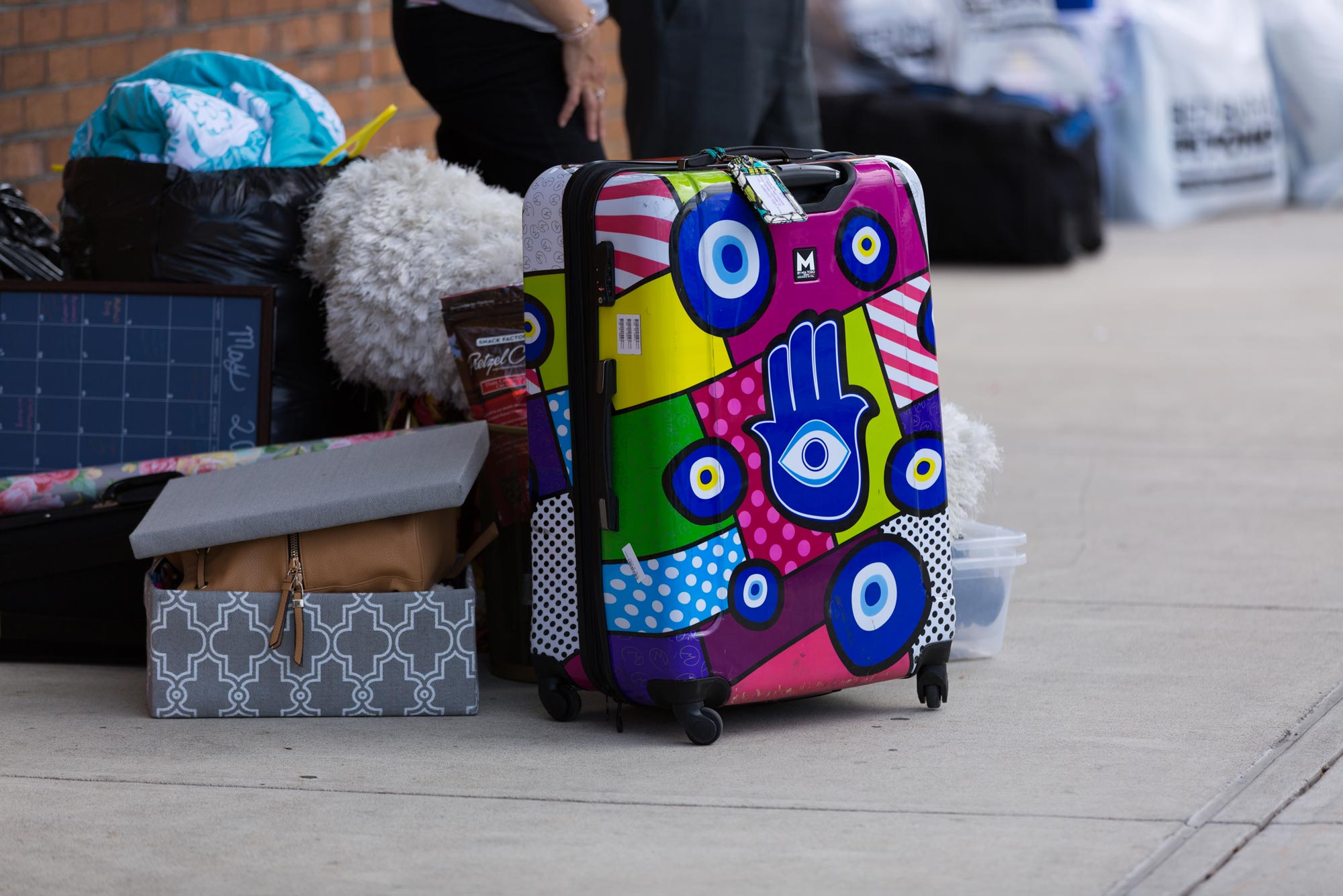 A photo of a student with their suitcase on BU move in day