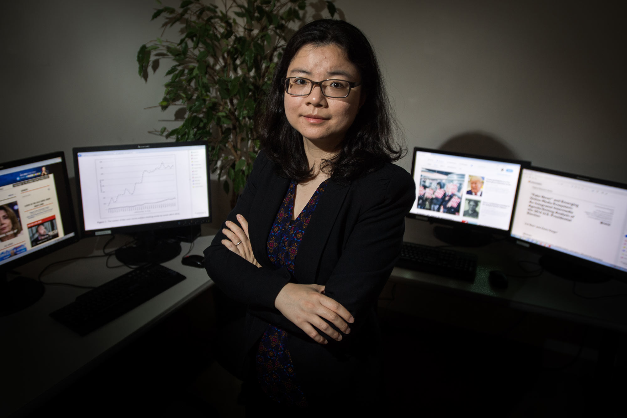 A photo of Lei Guo with her arms crossed in front of a bank of computer monitors