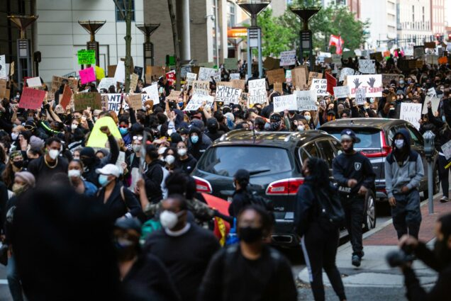 Photo of people took to the streets of Boston on May 31, 2020, protesting the murder of George Floyd. Protesters marched through Tufts Medical Center. Some are seen on sidewalks, a line of parked cars is seen, with most protestors in the streets holding signs.