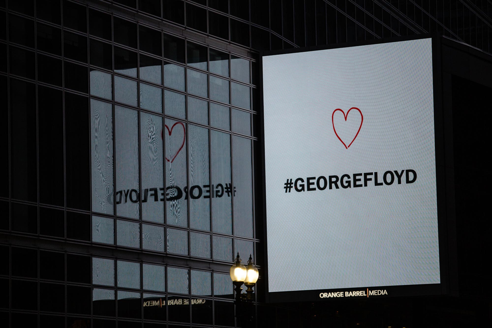"A digital sign overlooking protests in downtown Boston that reads ""George Floyd"" with a heart above the text"