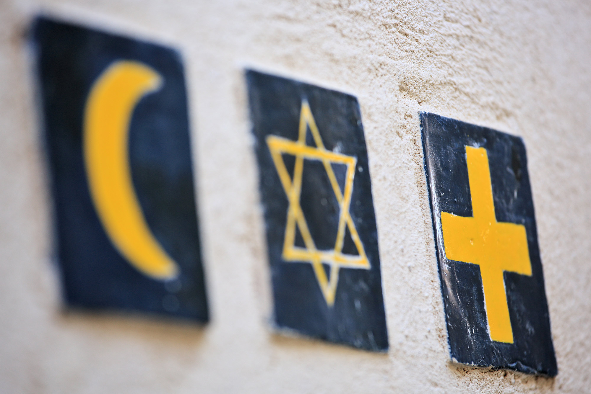 An image of an Islam crescent, Star of David, and Christian cross