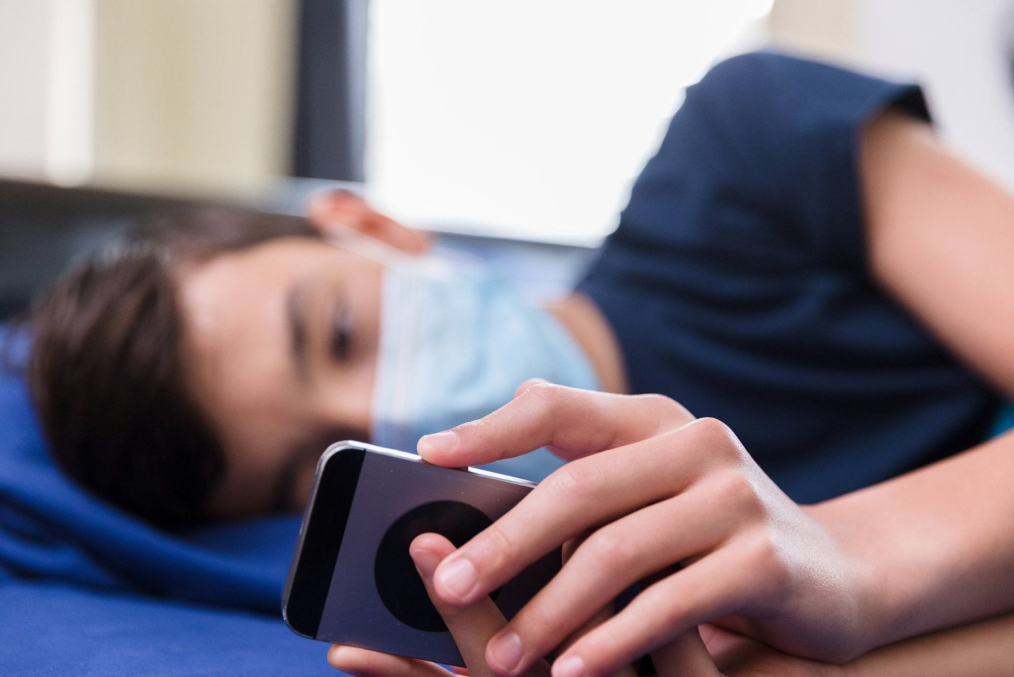 During COVID-19 pandemic, a teen wearing a protective mask lies in bed watching a video on his smart phone. His face is blurred.