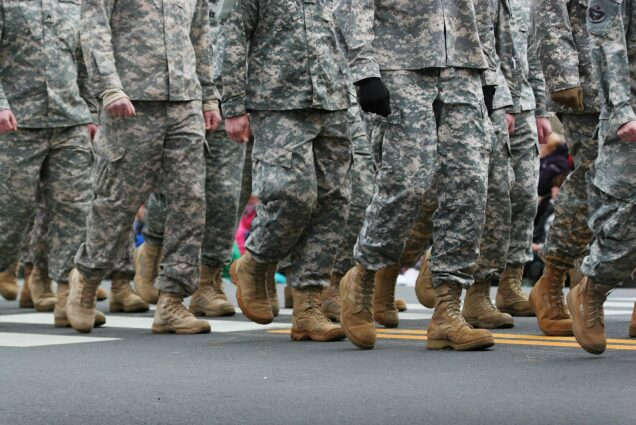 Image of soldiers dressed in army camouflage in an army parade. In the shot, only the road, army boots, and lower half of the soldiers are seen.
