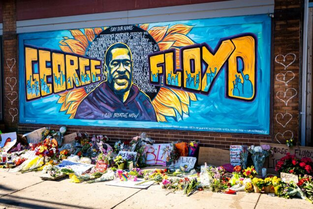 "Brightly colored mural honoring George Floyd created during the Black Lives Matter protest in Minneapolis, Minnesota. The mural is a painting of Floyd with a sunflower behind him like a halo. ""George Floyd"" painted on either side of his portrait."