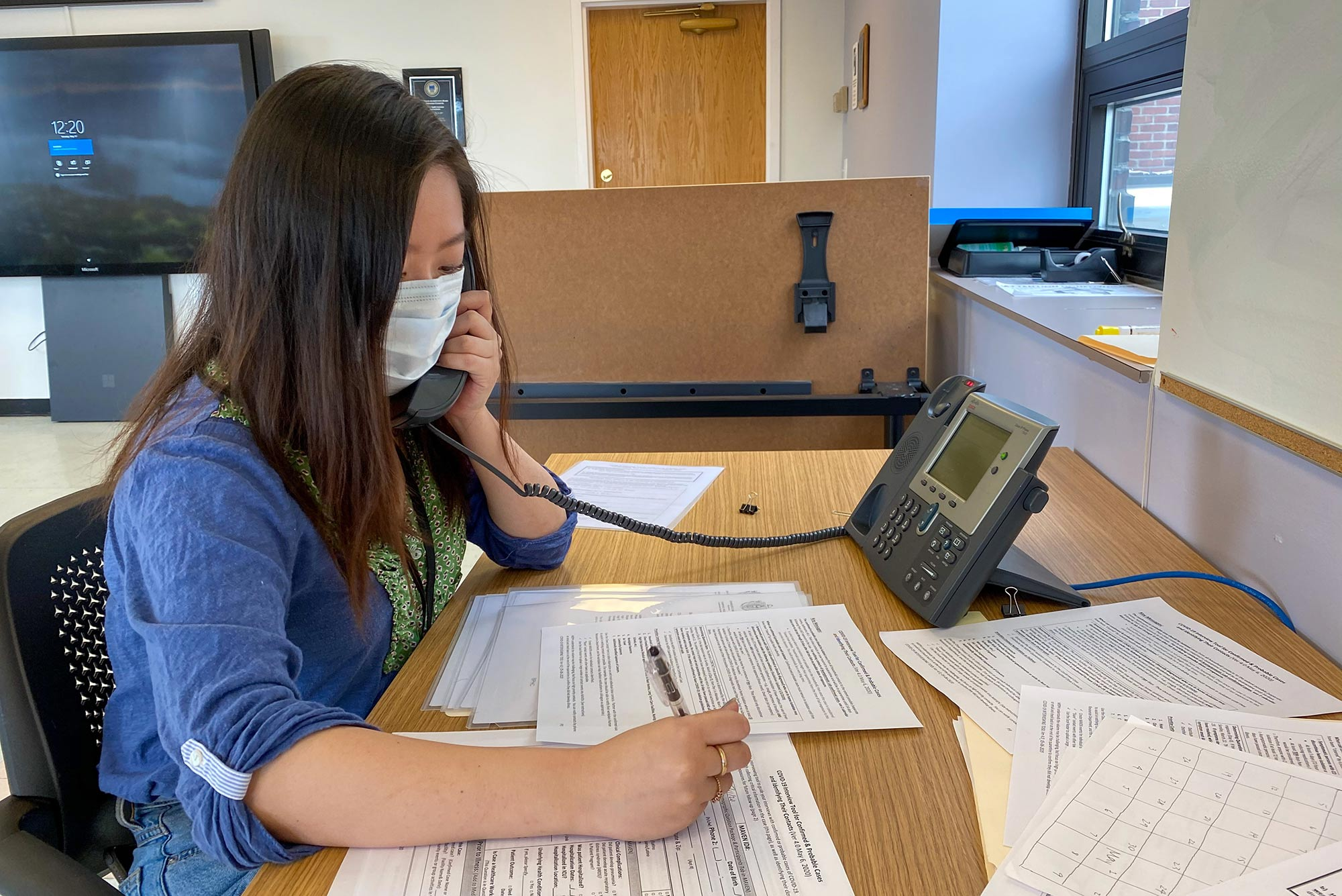 Image of Rinka Murakami (SAR'20, MPH'21) volunteering as a contact tracer for the city of Boston. Murakami wears a mask, writes on some forms, while talking on the phone.