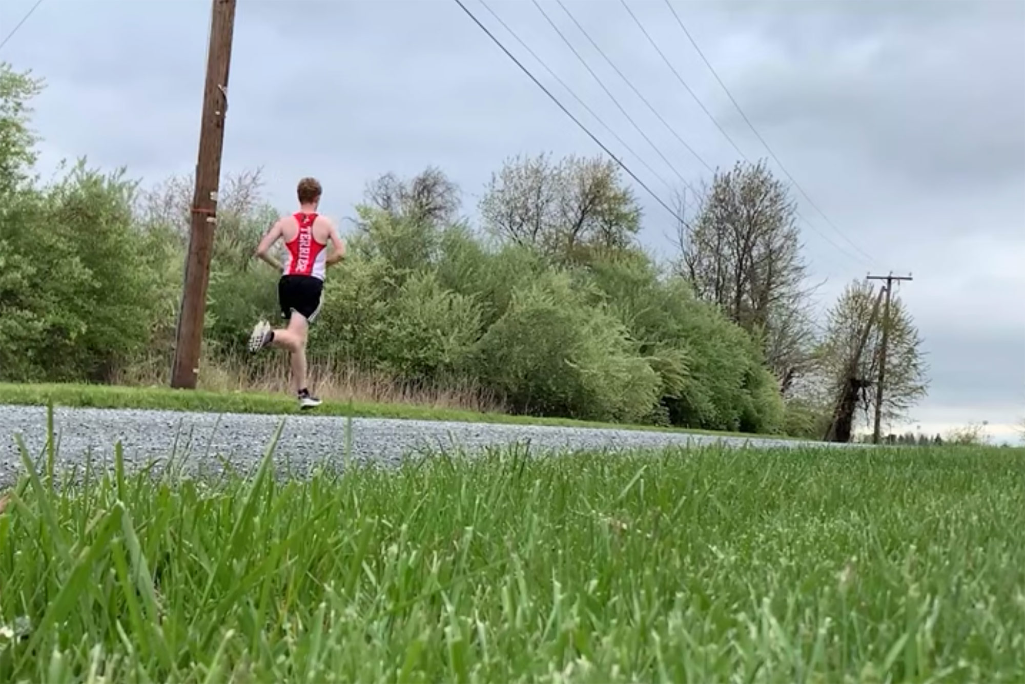 Photo of long-distance runner, Rylan Pettit (ENG'23), running down a street. Grass is seen in the foreground, Pettit wears his BU jersey. Pettit made a video discussing his improvised training regimen when the pandemic sent him home to Virginia for remote learning.