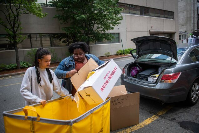 "Photo of Katerina Chew (left) (MET 20) and Robyn Volcy-Lee (SAR 20, SPH 21) pack up their car on June 1, 2020. Students were able to return to campus to pick up their belongings. Volcy-Lee holds a ""Property of Boston University Box"" as Chew holds a yellow moving cart."