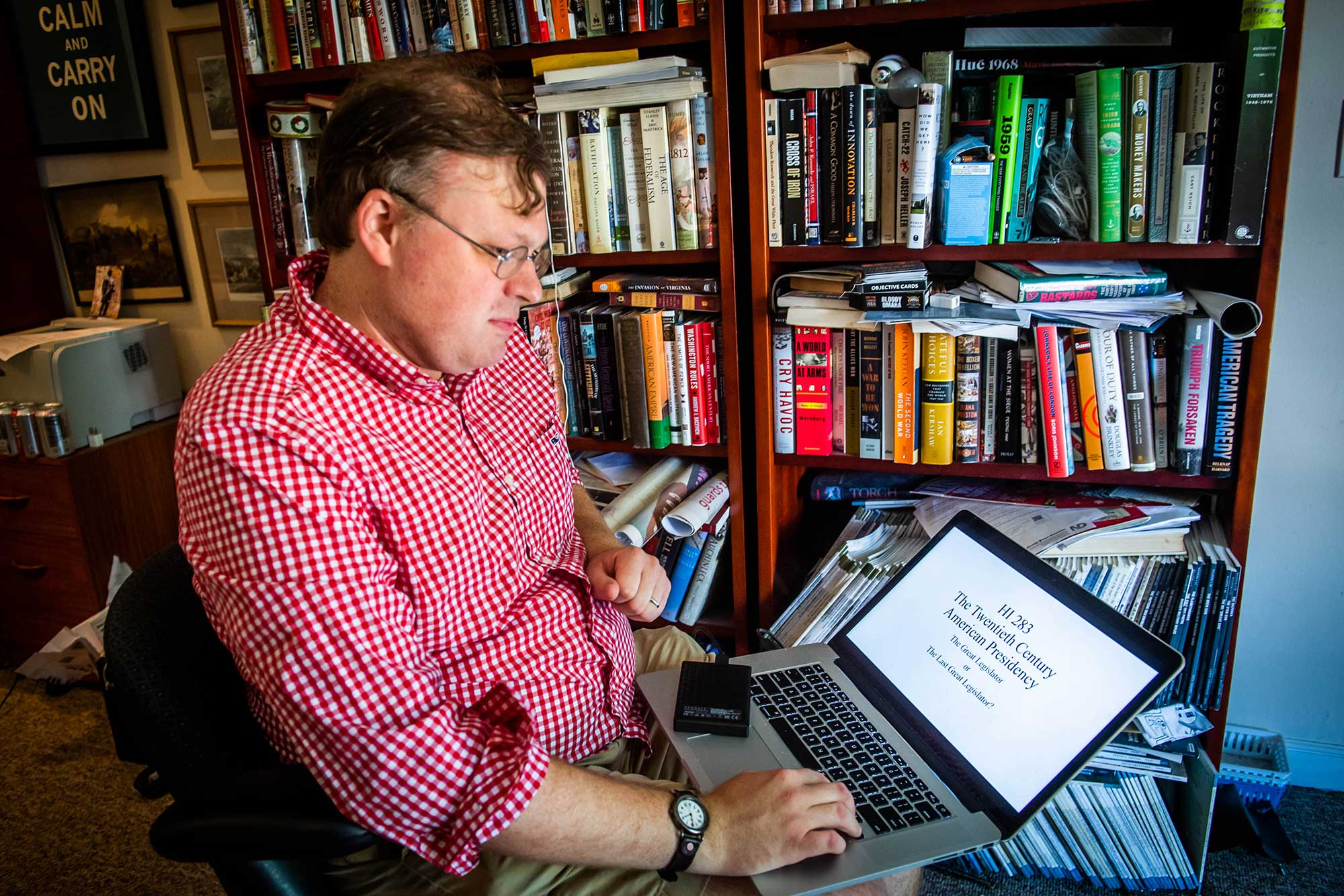 A photo of Andrew David working from his Watertown home on his laptop teaching his class on the history of the American presidency.