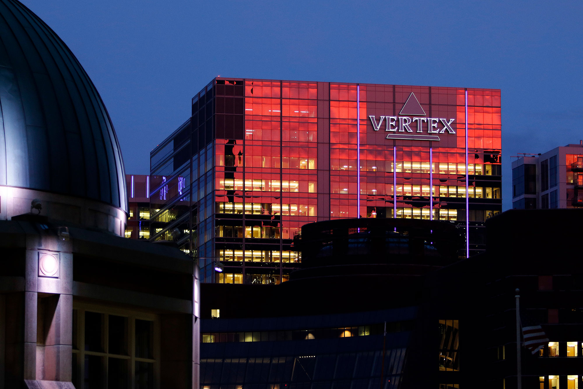 The sunset reflects off the Vertex Pharmaceuticals headquarters building, Thursday, Sept. 21, 2017 in Boston's Seaport. A sign on the building reads 'Vertex' in purple. The top dome of a building is seen in the bottom left foreground.