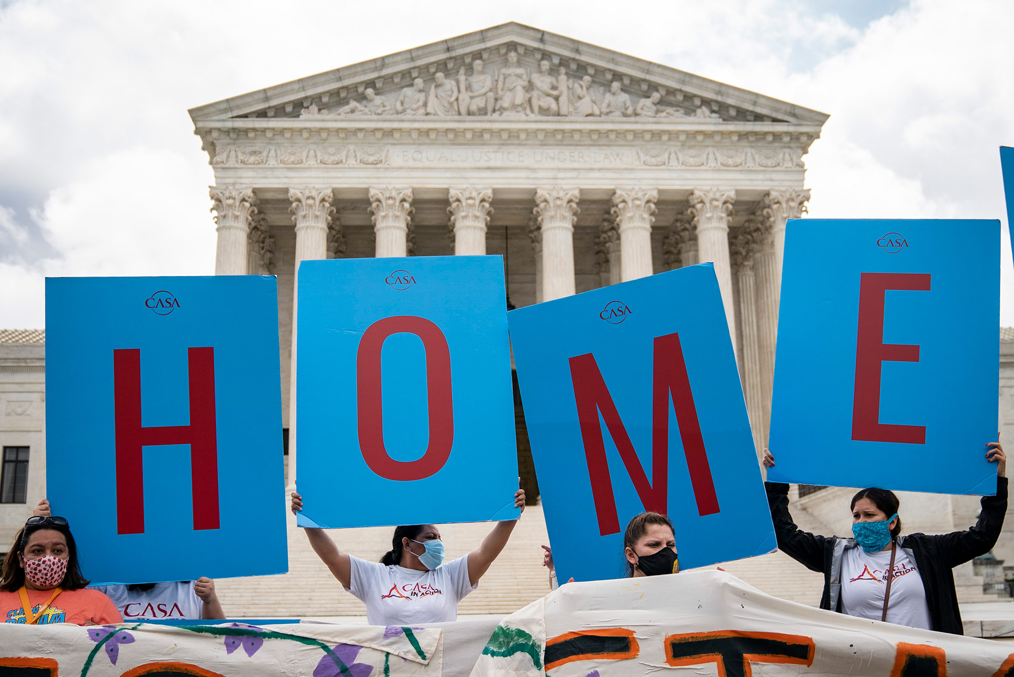 "Photo from Washington, DC on June 18th. Pictured are DACA recipients and their supporters rallying outside the U.S. Supreme Court on June 18, 2020 in Washington, DC. They hold a blue signs with red letters that read ""HOME"" On Thursday morning, the Supreme Court, in a 5-4 decision, denied the Trump administration's attempt to end DACA, the Deferred Action for Childhood Arrivals program."
