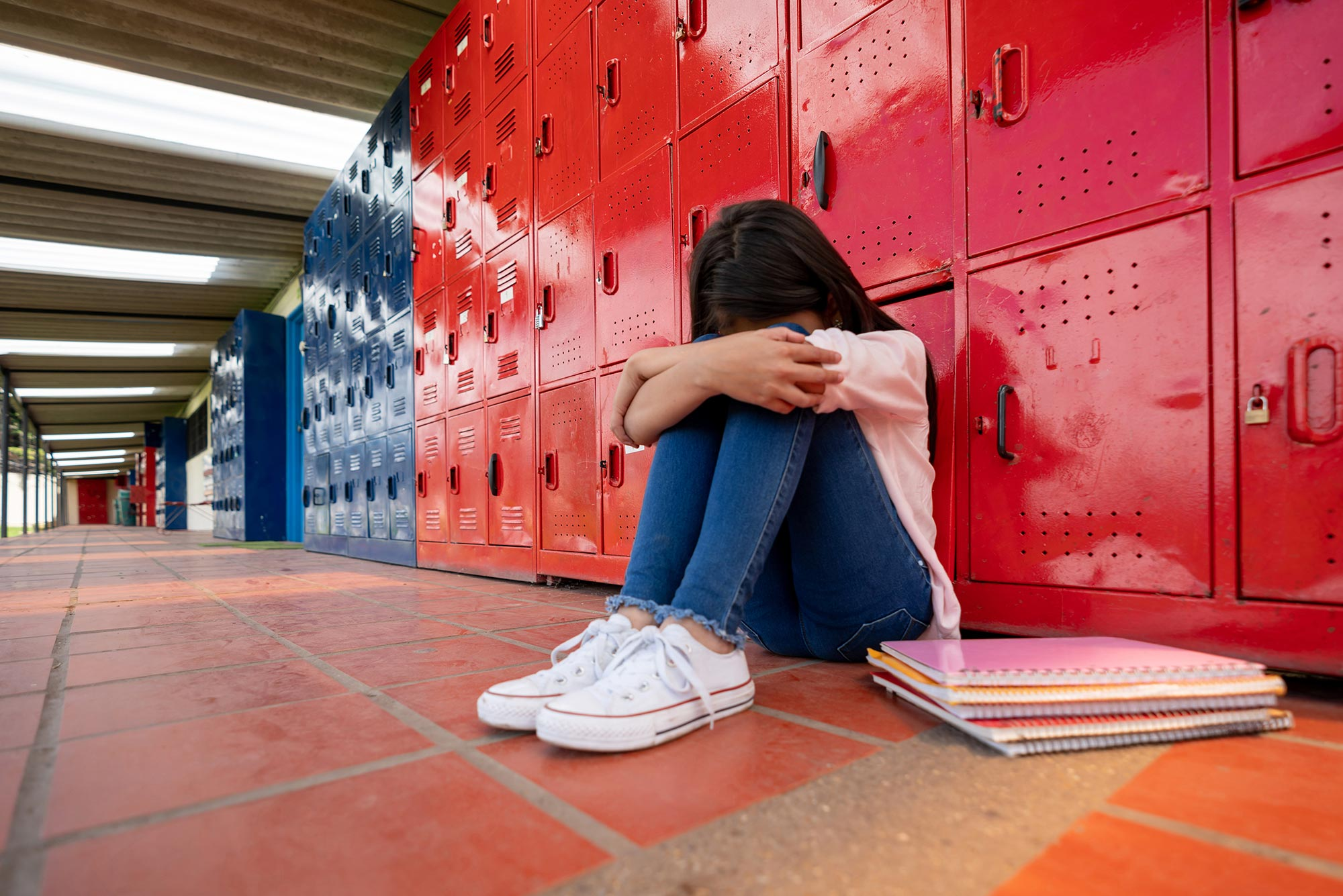 A photo of a child sitting against a bank of lockers with their head down