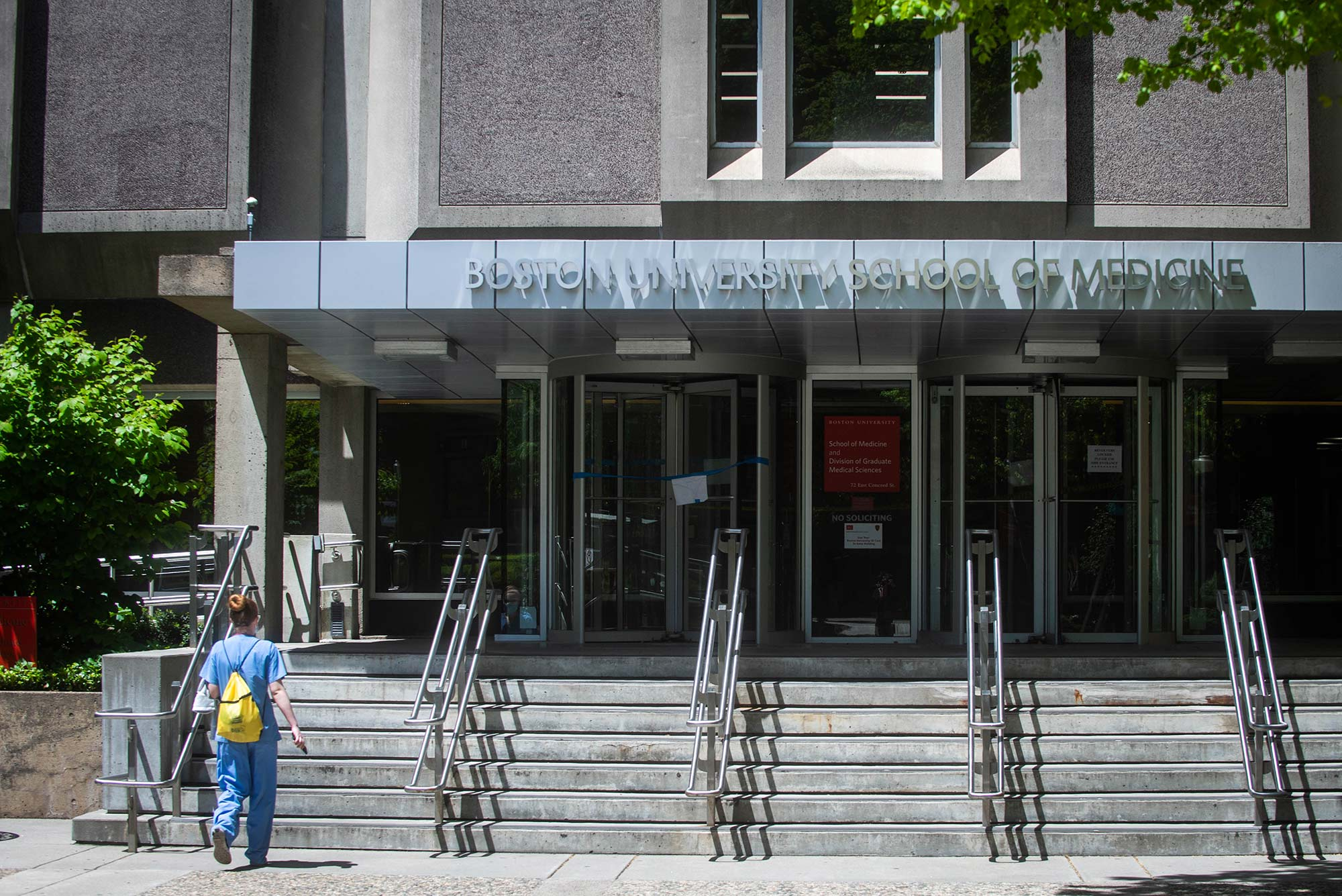 Photo of the exterior of the Boston University School of Medicine on Tuesday, May 19, 2020. A person in scrubs wearing a small yellow backpack walks up the stairs towards the front door.