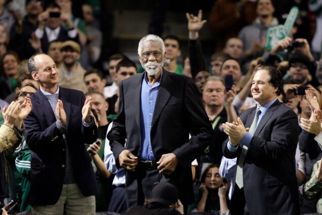 Photo of Former Boston Celtic Bill Russell, middle, receiving a standing ovation after being introduced prior to the Celtics' NBA basketball game against the Detroit Pistons in Boston, Wednesday, Feb. 15, 2012. Fans clap around Russell, who wears a suit jacket and blue button down.
