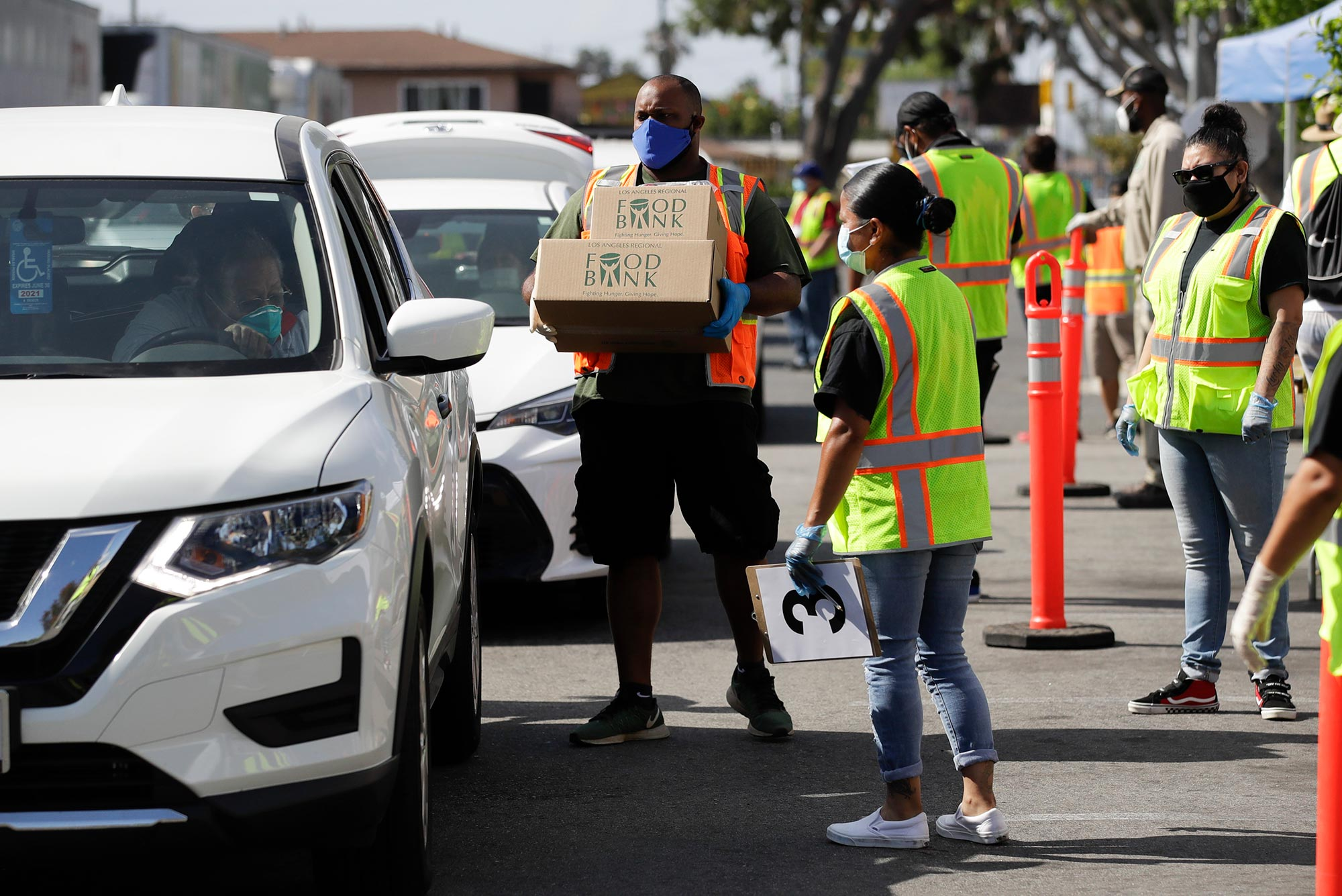 A photo of workers and volunteers loading up vehicles at a food distribution center in Compton, Calif.
