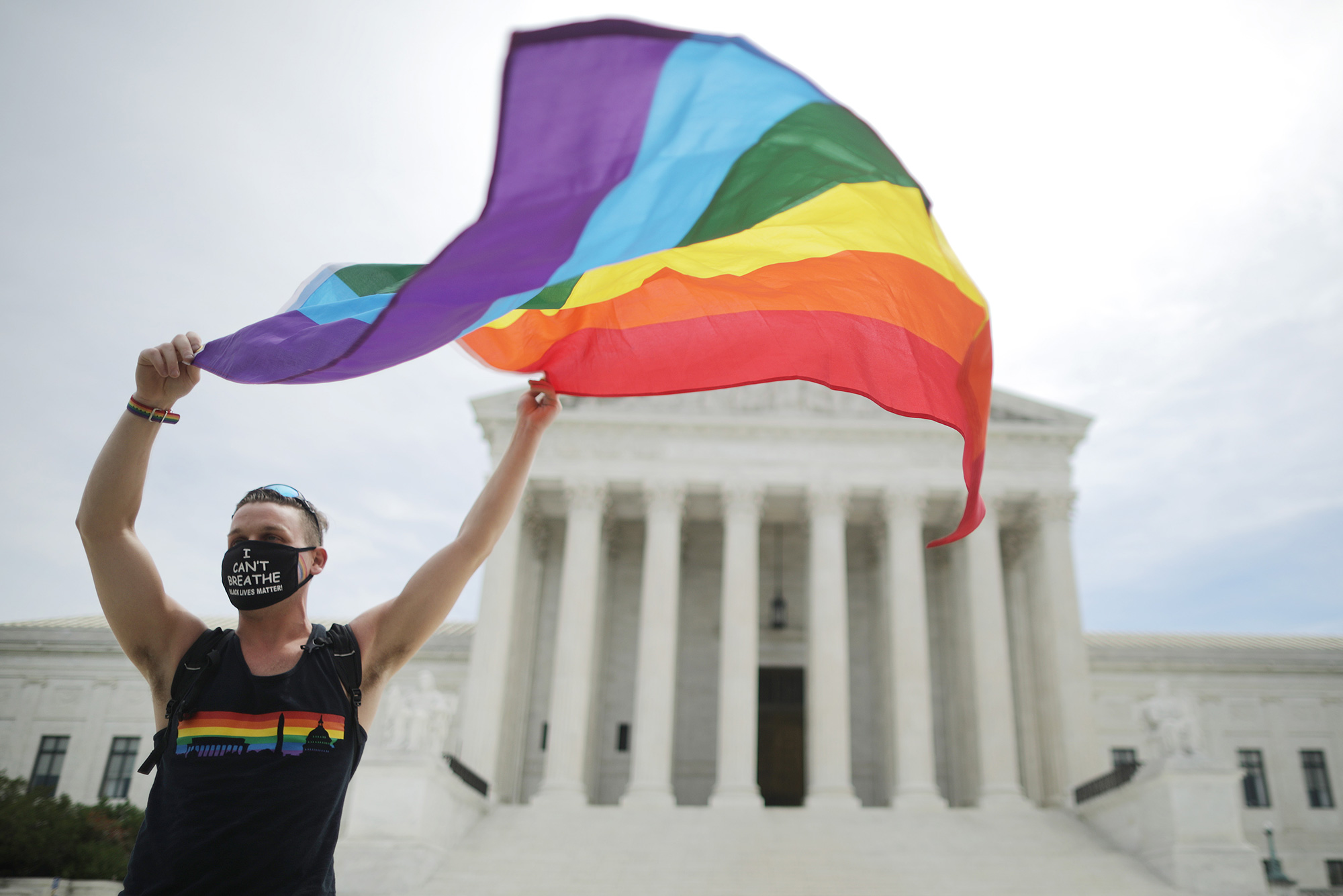 A person waving a rainbow Pride flag outside the Supreme Court building