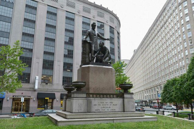 Photo of the Emancipation Statue in Park Square with Abraham Lincoln on May 21, 2013 in Boston, MA. The statue depicts Lincoln with his hadn extended as a man of color kneels at his feet. The buildings of Park Square and an overcast sky are seen in the background.