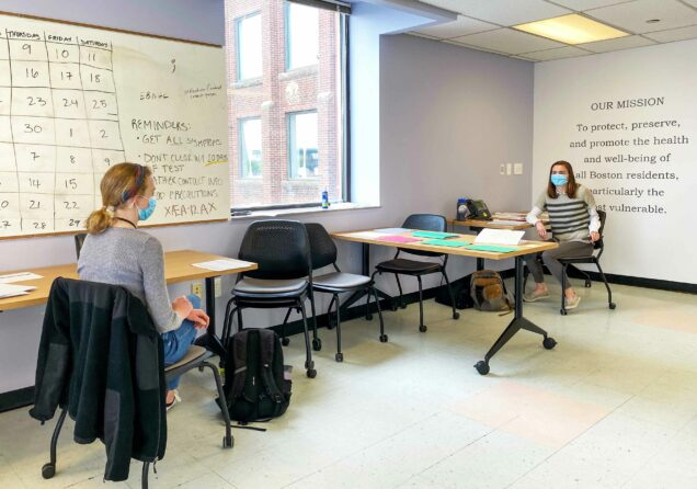 Jessica Schueler (SAR'21) and Natalia Kelley (SAR'22) volunteer as contact tracers as part of the city of Boston's coronavirus pandemic response. They are seen here, socially distant, at desks in an office. A white board and mission statement are seen on the walls.