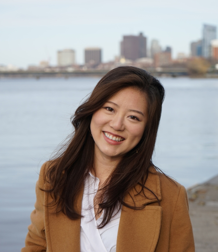 Portrait of Rinka Murakami (SAR'20, MPH'21 in a light brown blazer. A blurry city skyline and water is seen in the background.