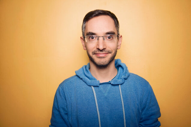 Portrait of Myq Kaplan. He wears a blue sweatshirt in front of an orange background.