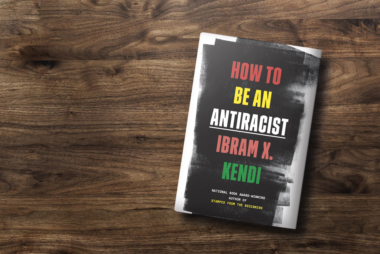 "Photo of the cover of ""How to Be An Antiracist"" by Ibram X. Kendi resting on a grainy piece of dark wood."