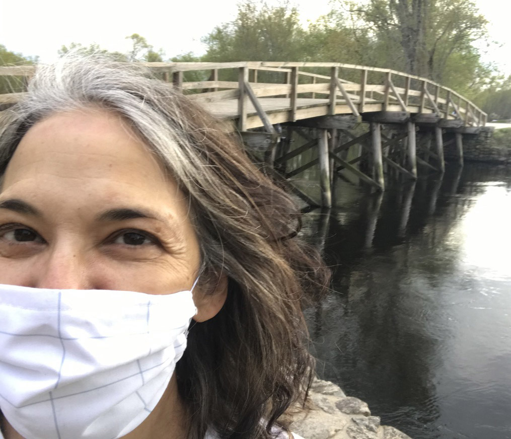 Melinda Lopez wearing a PPE mask standing in front of a bridge